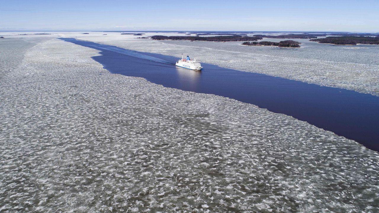 Vista aérea en la que se ve un ferry navegando a través del hielo derretido en el canal principal entre las islas del archipiélago Merenkurkku, en el oeste de Finlandia