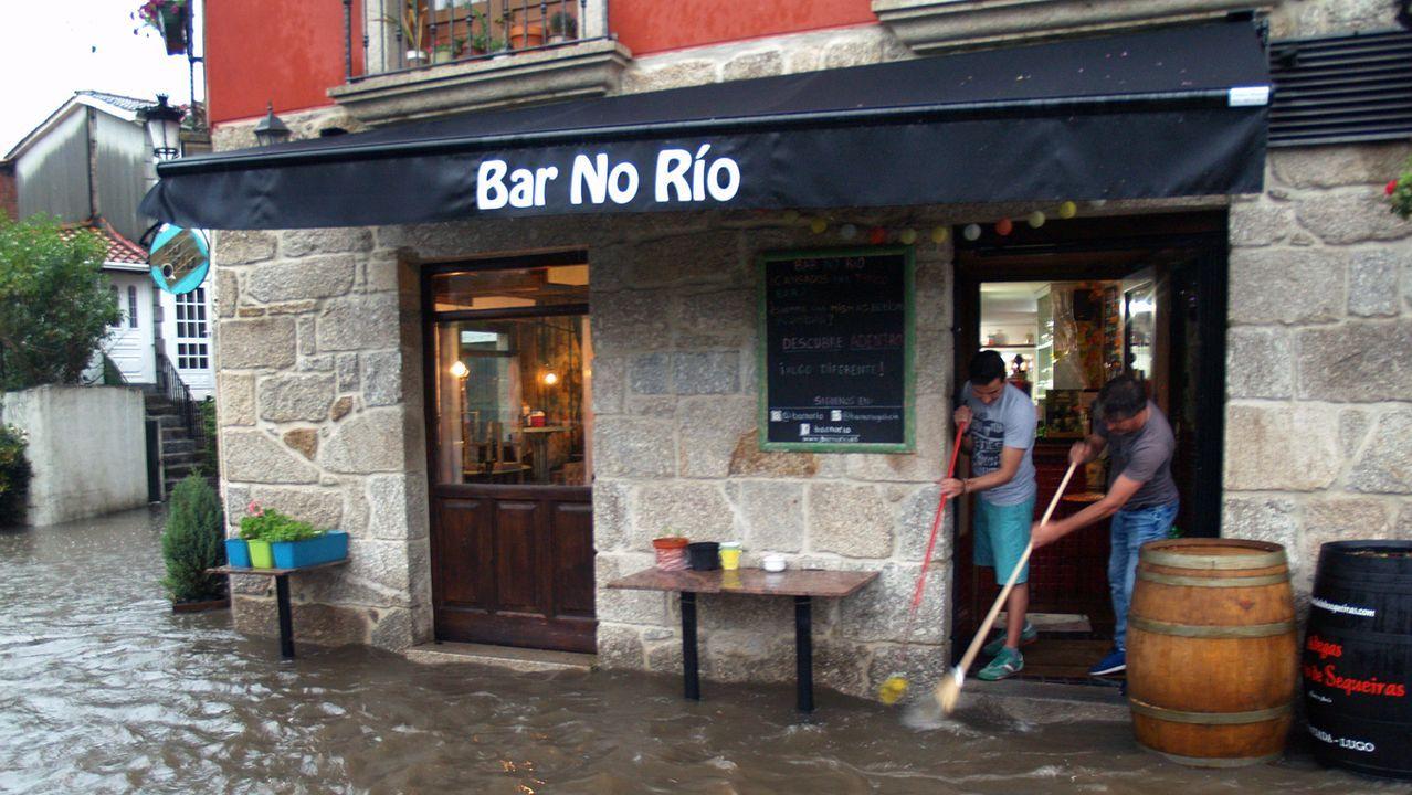 Los dueños del bar Río achican en Chantada el agua que entró en su local