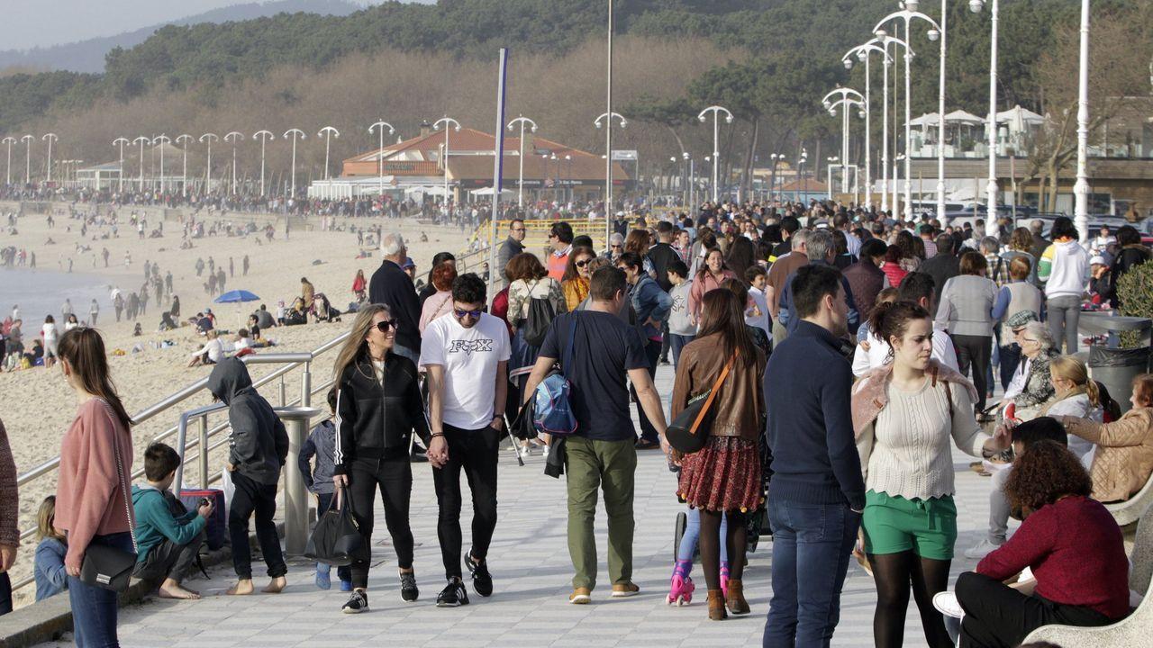 Galicia empieza a recibir más retornados que personas que se van. En la imagen de archivo, gente paseapor el paseo de la playa de Samil