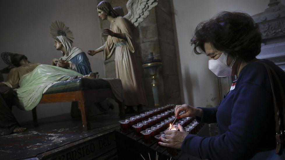 Una feligresa enciende una vela en la iglesia de San Francisco de Santiago