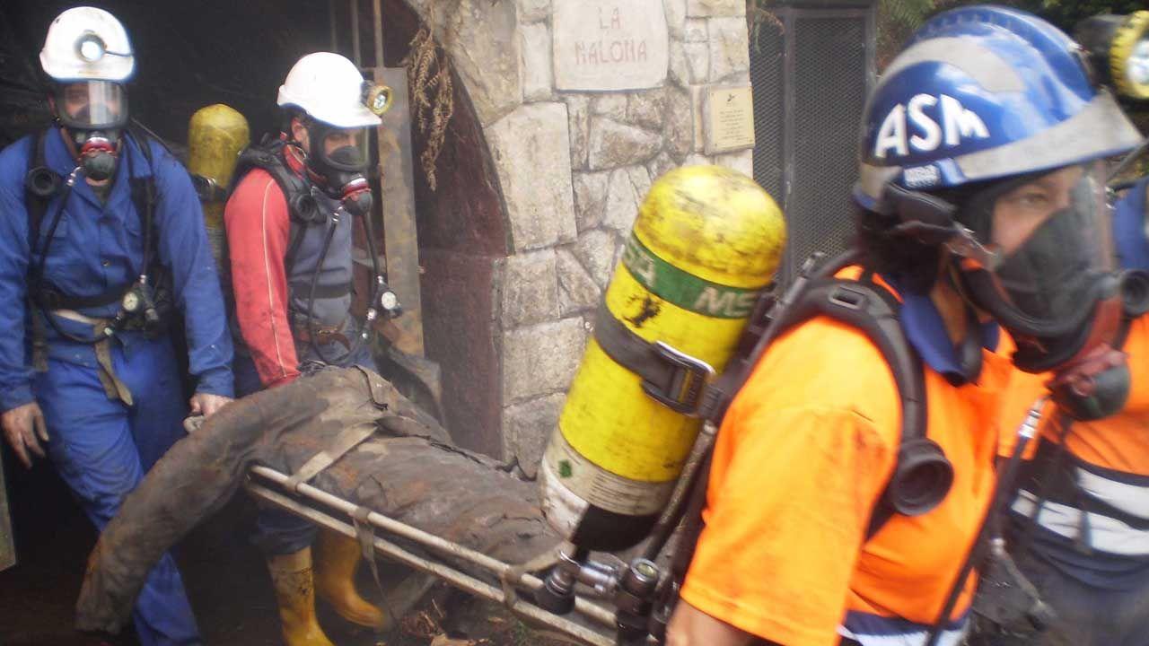 Un grupo de pasajeros consulta los vuelos en el Aeropuerto de Asturias.Brigada de salvamento minero
