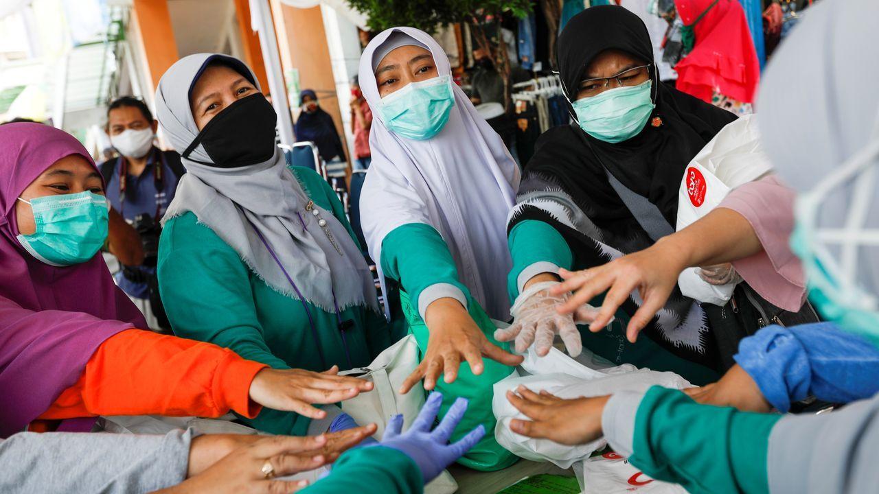 Un grupo de sanitarias indonesias se anima, antes de comenzar a realizar su trabajo en un mercado de Bogor