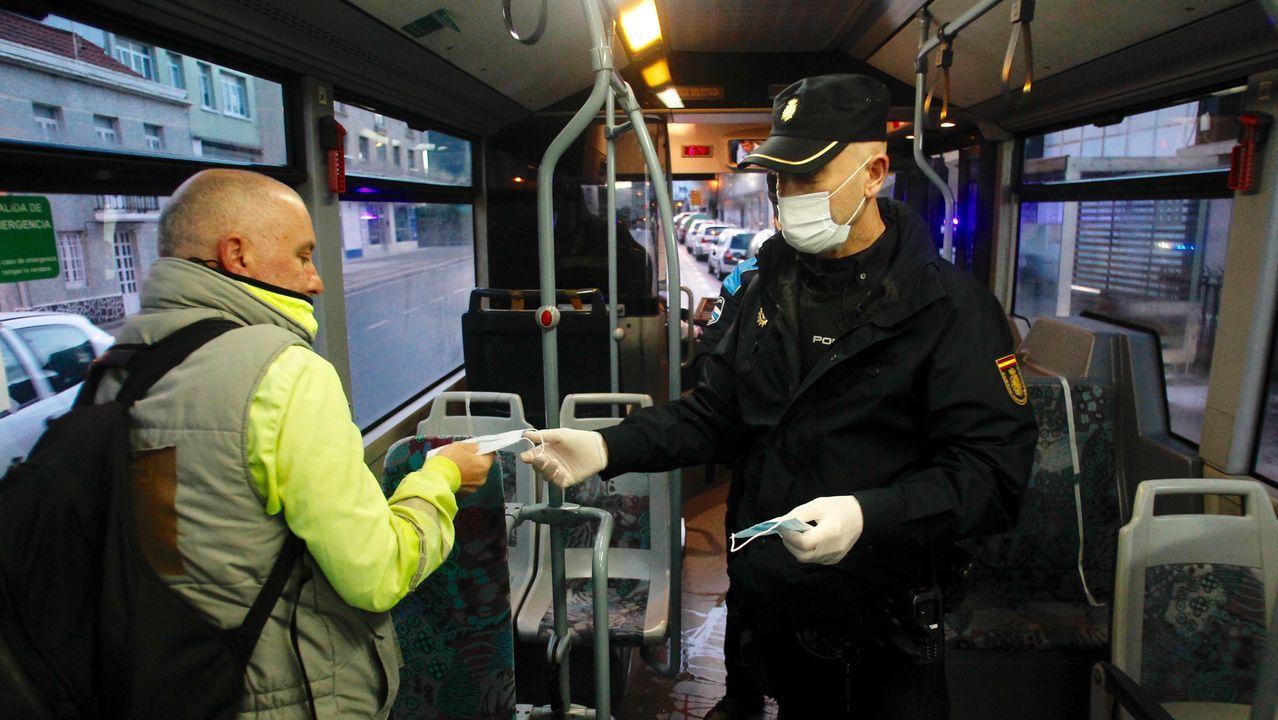 Policia local de Narón y Policía Nacional reparten mascarillas a usuarios del transporte público urbano en la carretera de Castilla en O Alto