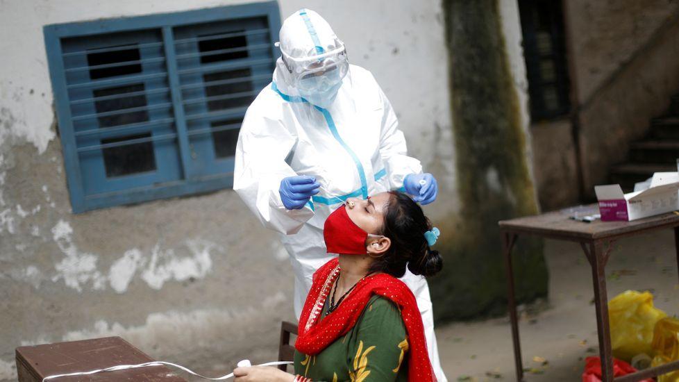 Un sanitario coge una muestra de saliva a una persona en una escuela de Nueva Dehli, India