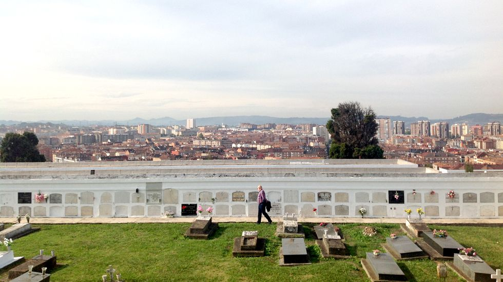 Un visitante del cementerio de Ceares, con Gijón al fondo