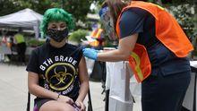 Los ejes comerciales de las ciudades.Una adolescente de 14 años recibe la vacuna contra el covid-19 en California