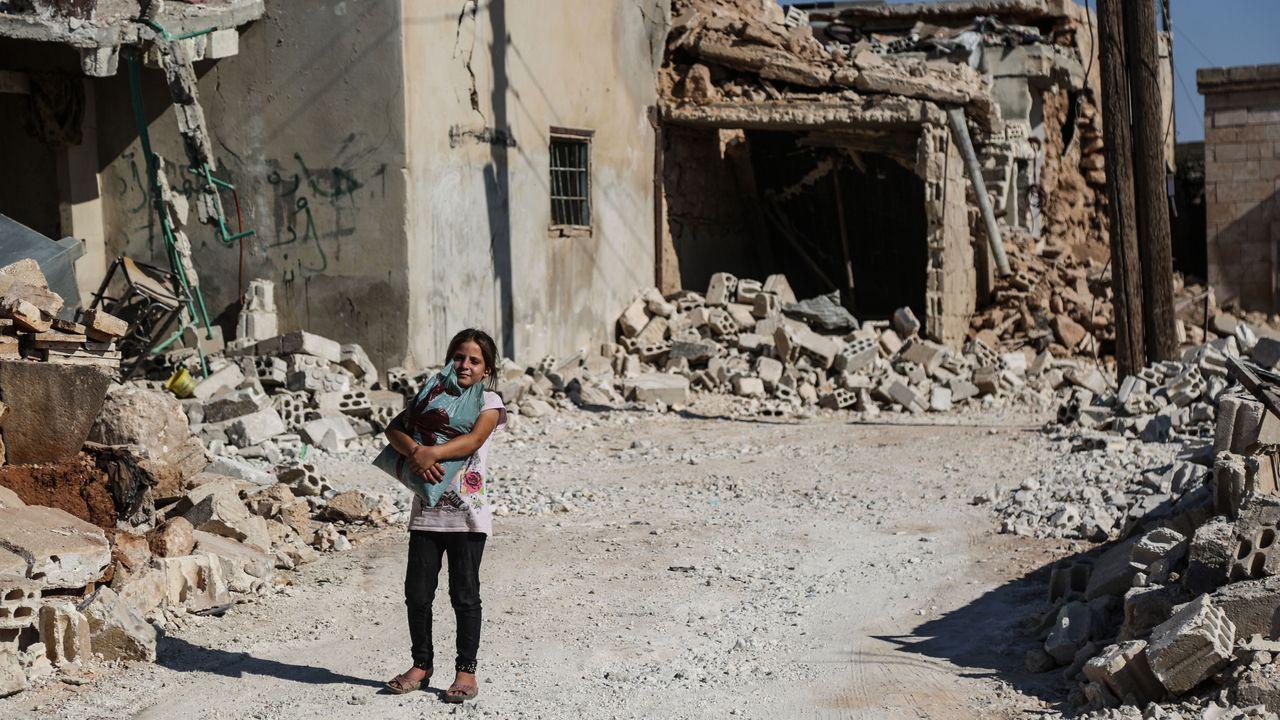 Una niña pasa por una zona de la ciudad de Tallmannis destruida por los bombardeos