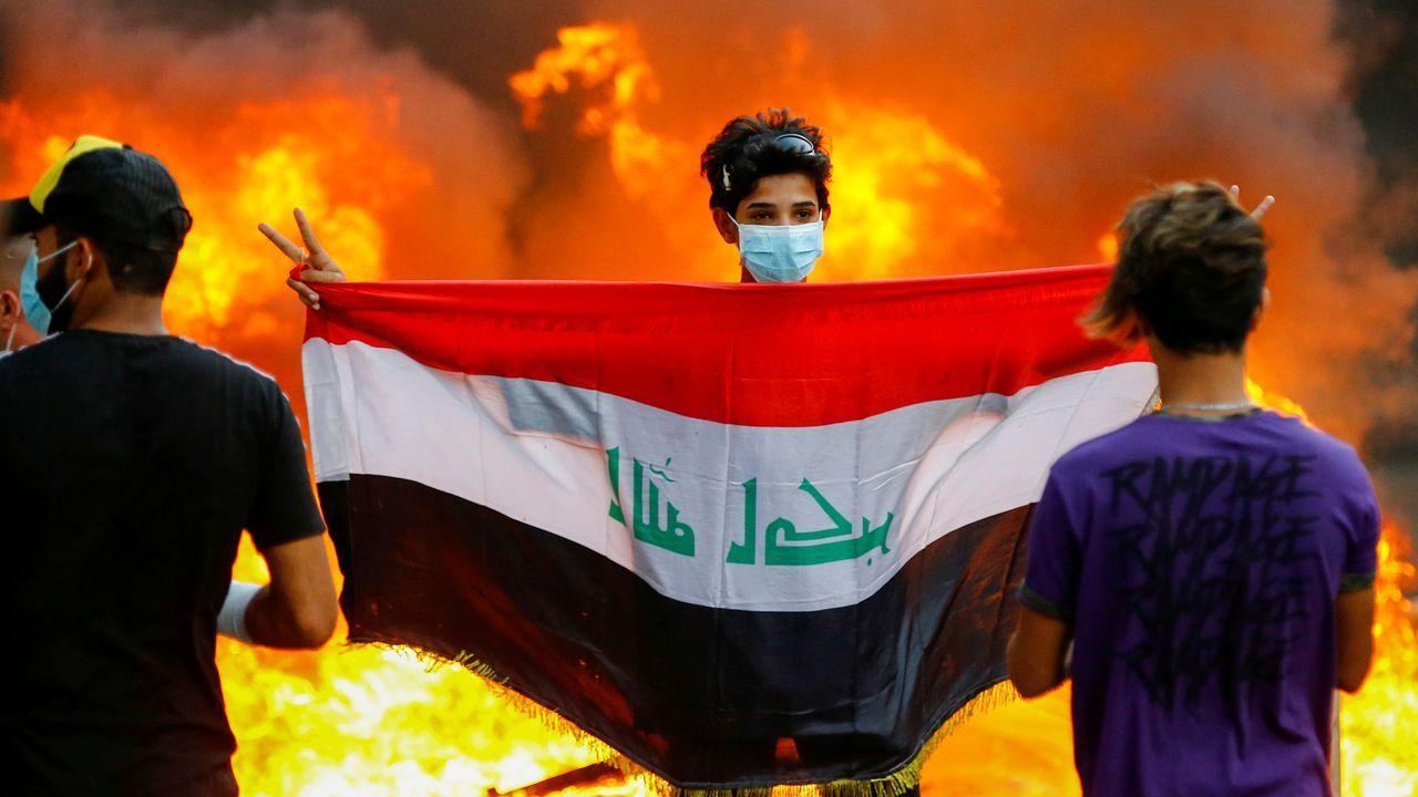 Un manifestante muestra la bandera iraquí durante las manifestaciones en Bagdad