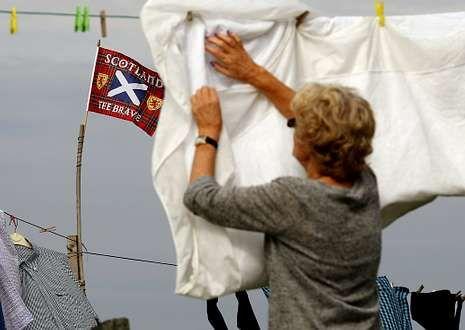 Una mujer extiende la colada en la isla de Lewis ante un emblema escocés.