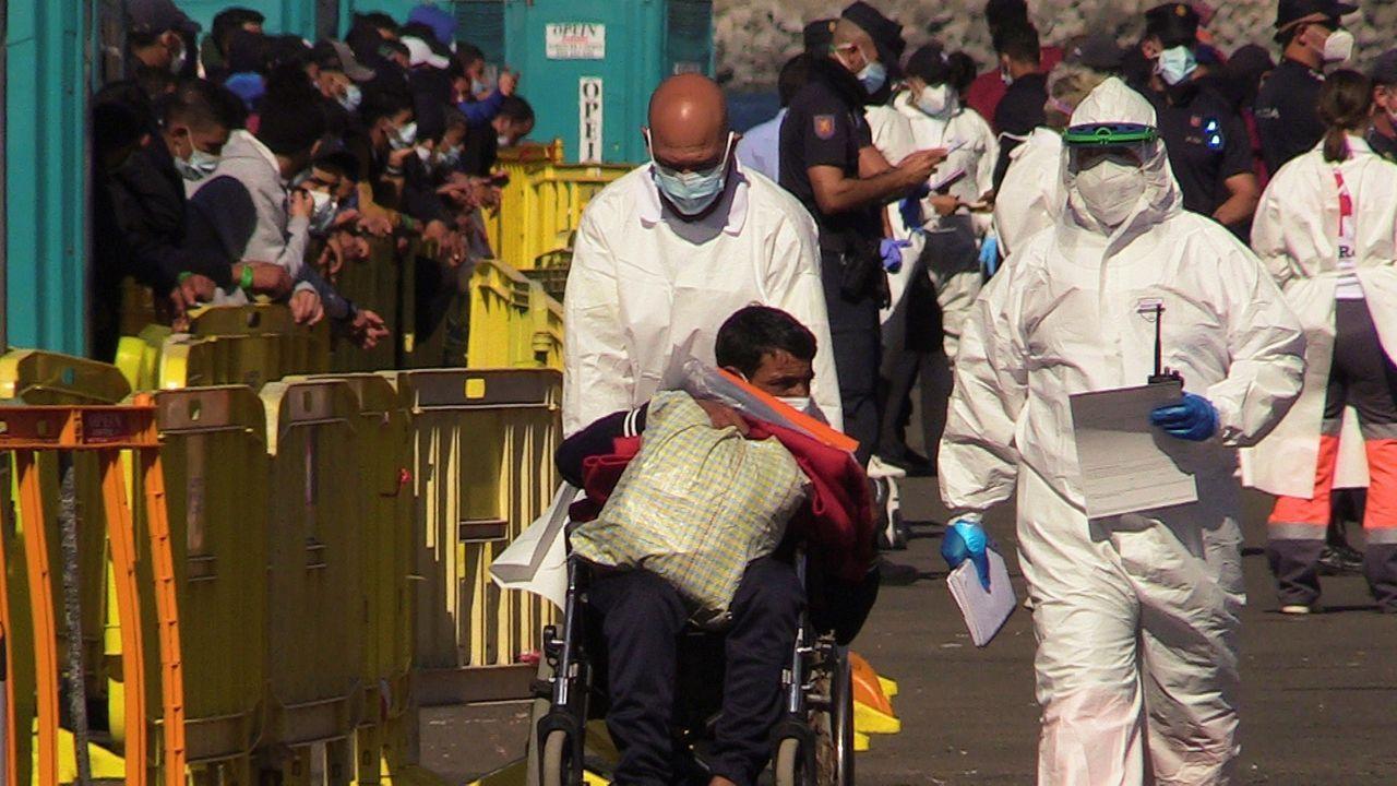 Los sanitarios atienden a un migrante a su llegada al puerto canario de Arguineguín, el pasado noviembre