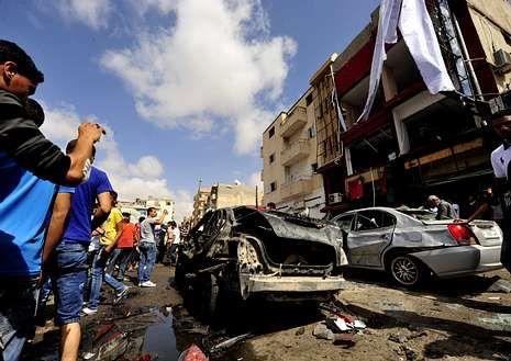 Habitantes de Bengasi observan el coche bomba.