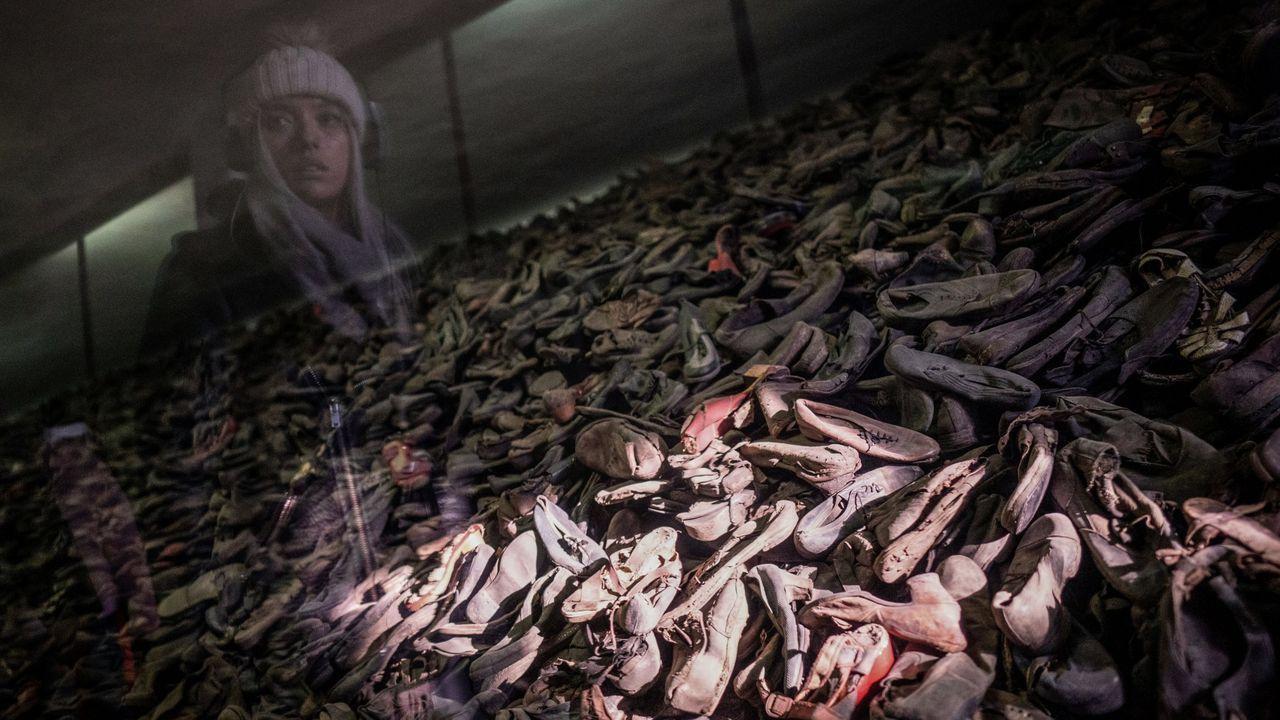 Una visitante observa un depósito de zapatos de prisioneros de Auschwitz en el museo del campo de concentración