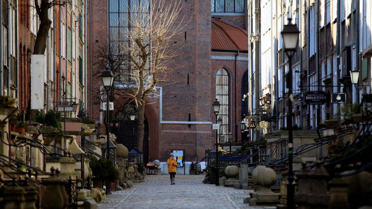 Una mujer camina en soledad por una calle de Gdansk, en Polonia