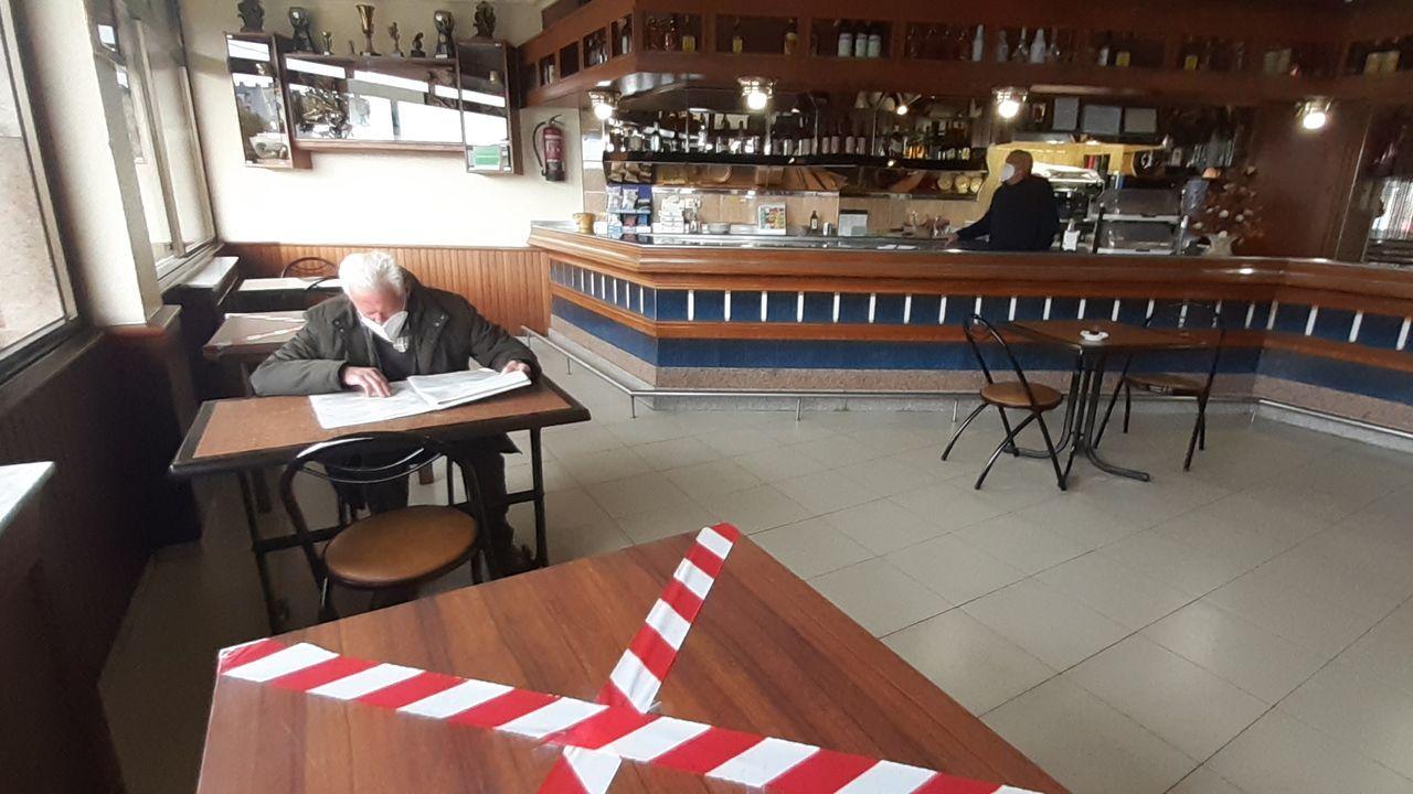 El surf retoma su actividad en Oleiros.Un cliente lee el periódico en la cafetería Ecuador