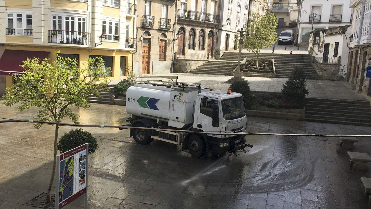 Un vehículo del servicio de limpieza lava el suelo de la plaza de España tras la declaración del estado de alerta
