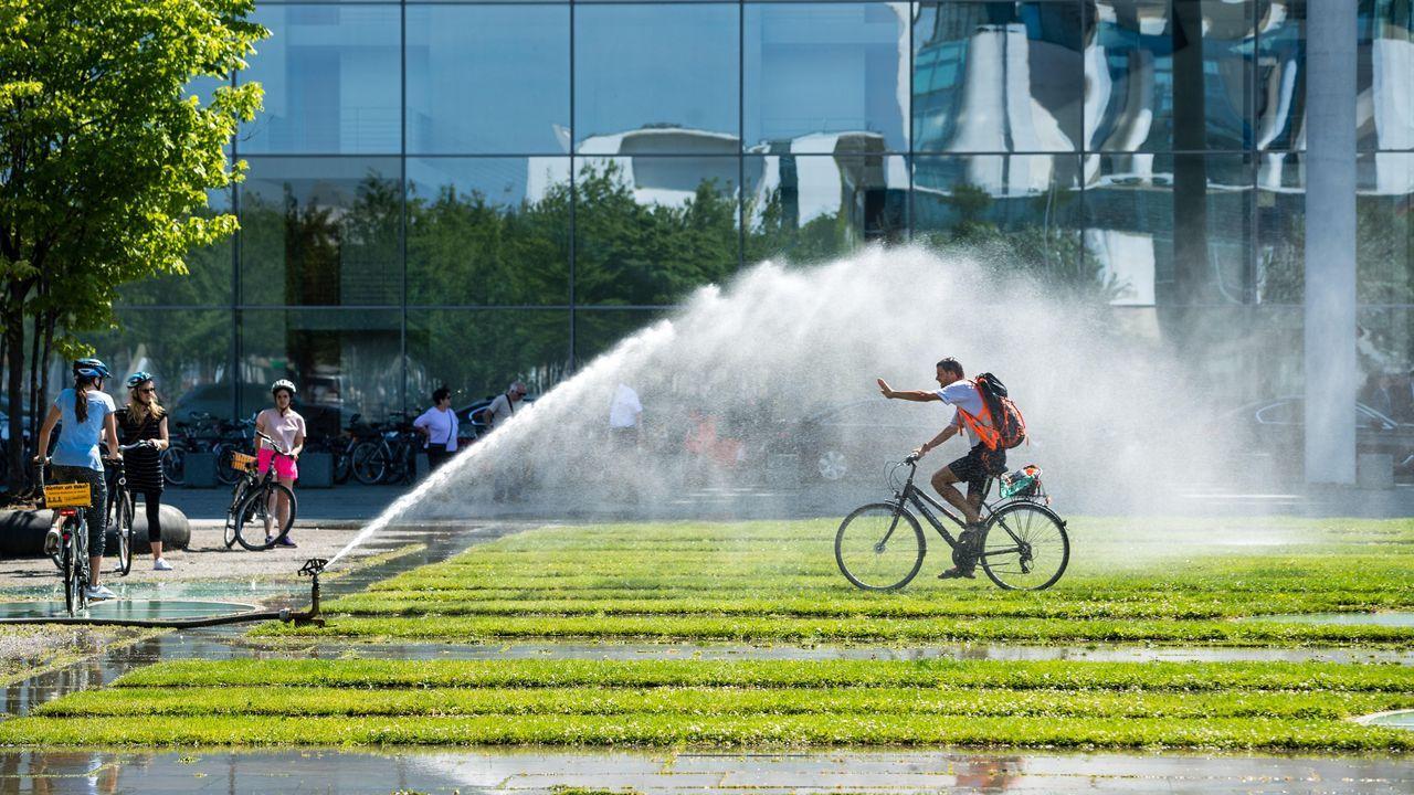 Un hombre en bicicleta se refresca con el agua de unos aspersores en Berlín, Alemania. Las temperaturas llegarán a los 40 grados centígrados esta semana según las previsiones meteorológicas.