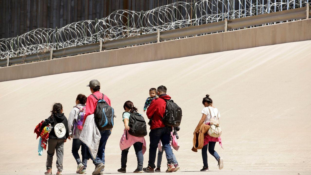 Un grupo de inmigrantes caminan por el muro fronterizo entre Ciudad Juárez y El Paso, después de cruzar el río Bravo