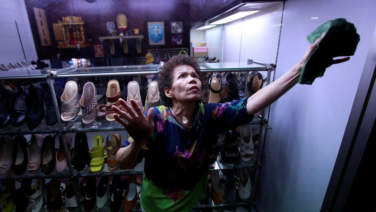 Una mujer limpia una ventana en una zapatería en Bangkok, Tailandia.