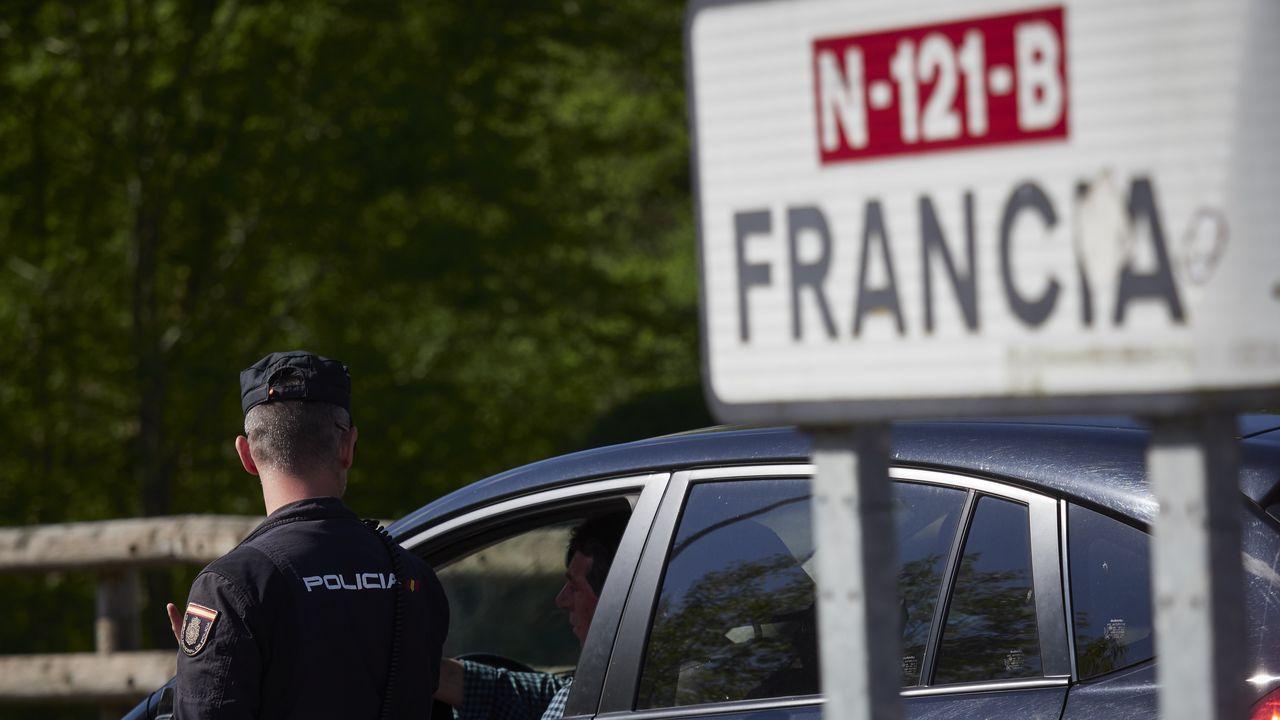 Un cartel señala la dirección a Francia mientras un policía interroga a un conductor en un control en la frontera navarro-francesa.