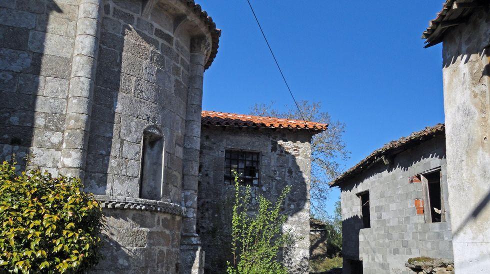 Construcción de cemento al lado de una iglesia románic aen O Saviñao.