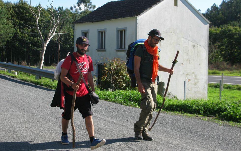 Dos peregrinos pasan ante la casa que el Concello de Negreira quiere para servicio de los romeros.