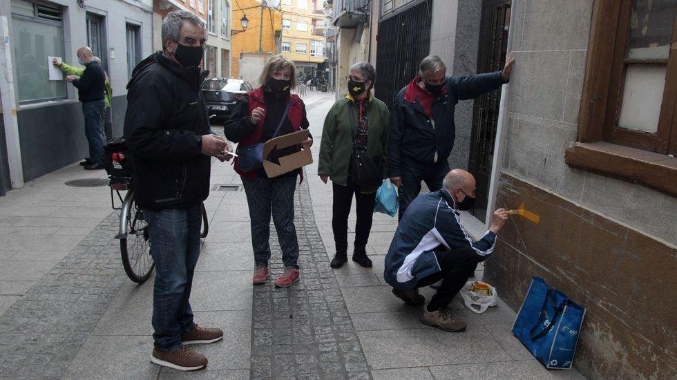 Voluntarios de una asociación de amigos del Camino de Invierno pinta flechas amarillas a su paso por Monforte