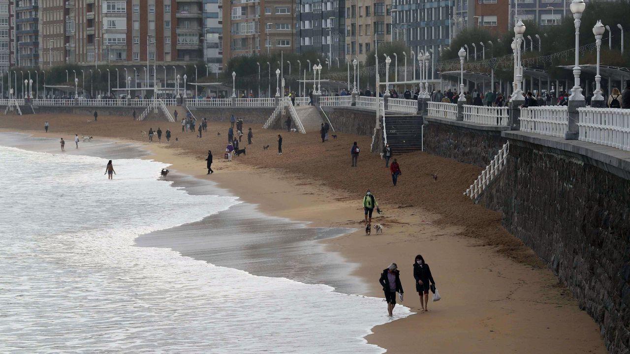 gasolinera, repostar, gasolina, estación de servicio.Varias personas caminan por la playa de San Lorenzo de Gijón