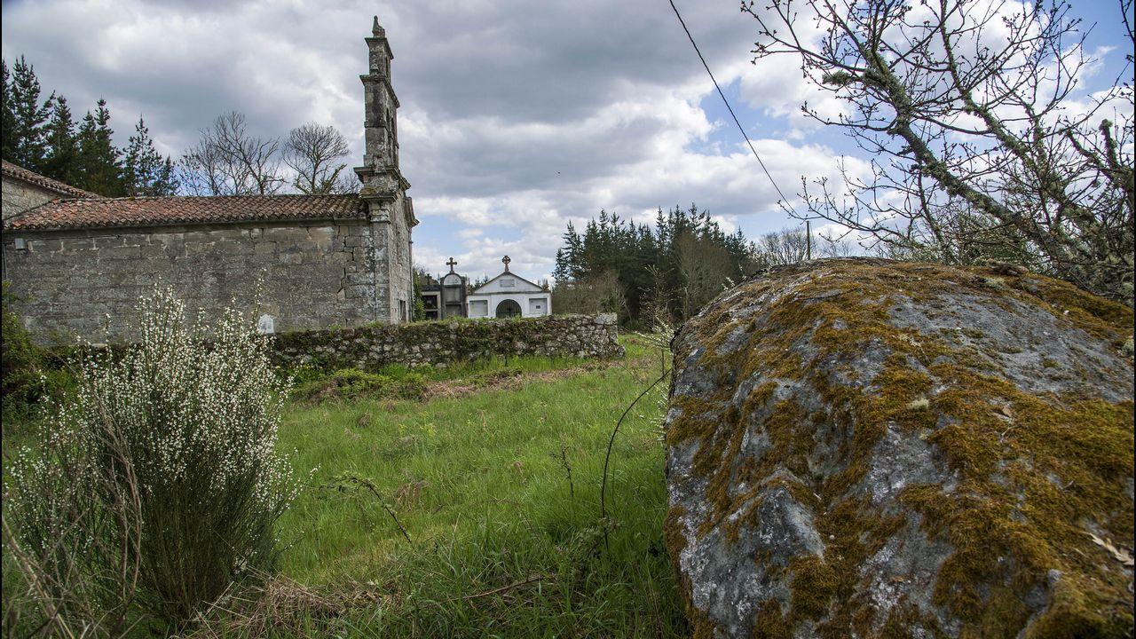 La iglesia de San Xulián y, en primer término, un peñasco con petroglifos
