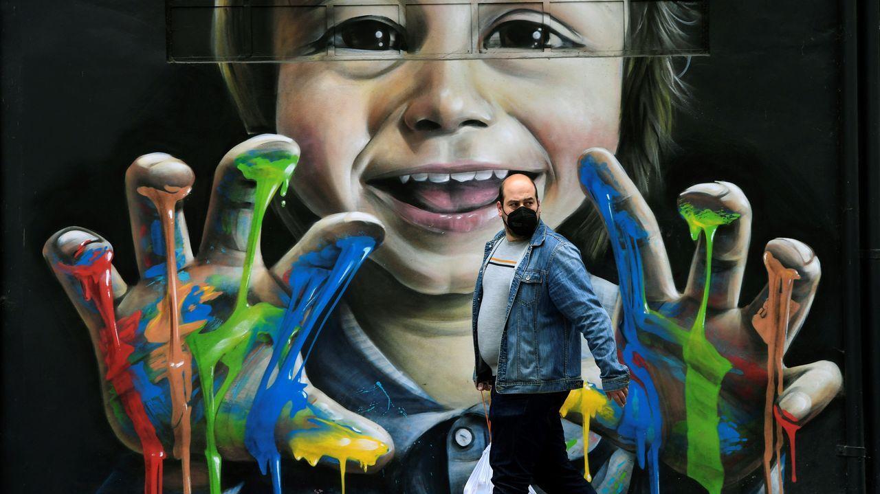Un hombre pasea junto a un grafiti del artista callejero Bastian Prendes en una calle de Pola de Siero