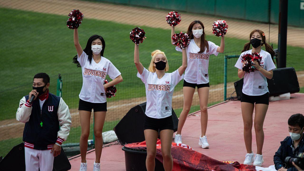 Las animadoras del equipo de béisbol coreano SK Wwyverns llevan mascarilla