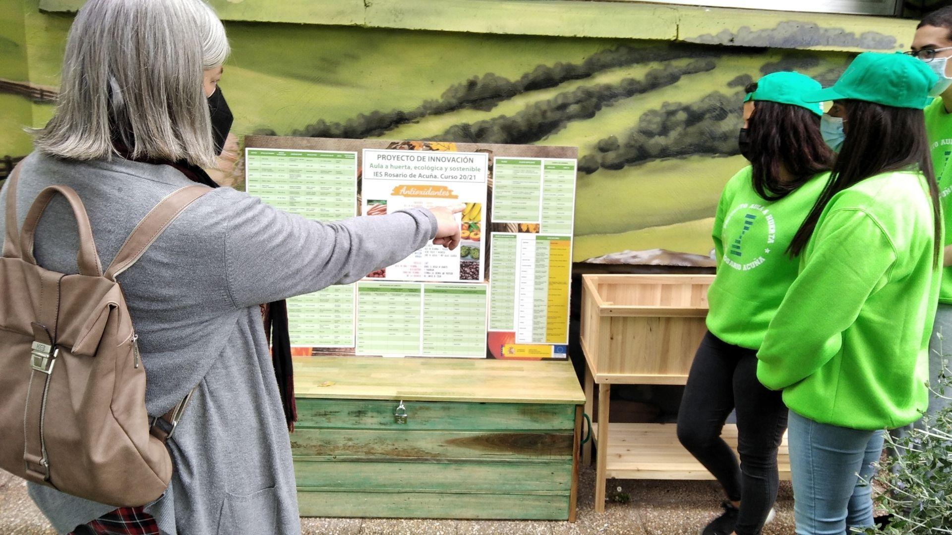 huerto escolar asturias.Clara Rosa Rodríguez señala el panel con las asociaciones de la huerta ecológica