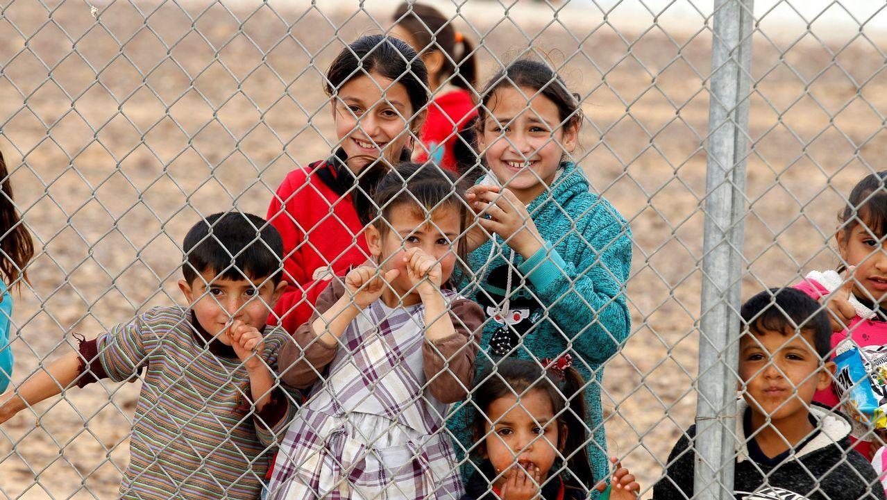 El Papá Noel más solidario.Varios nifos refugiados sirios observan a través de una valla en un campo de refugiados en Azraq, Jordania, el 29 de enero del 2018.