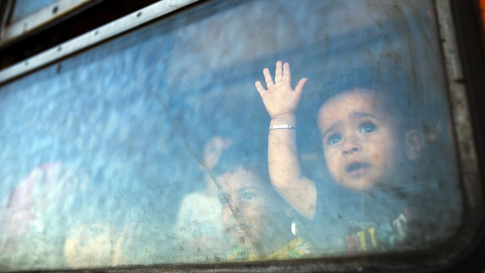 Un pequeño inmigrante mira a través de un tren de camino a Serbia en un nuevo viaje de inmigrantes en la frontera entre Grecia y Macedonia