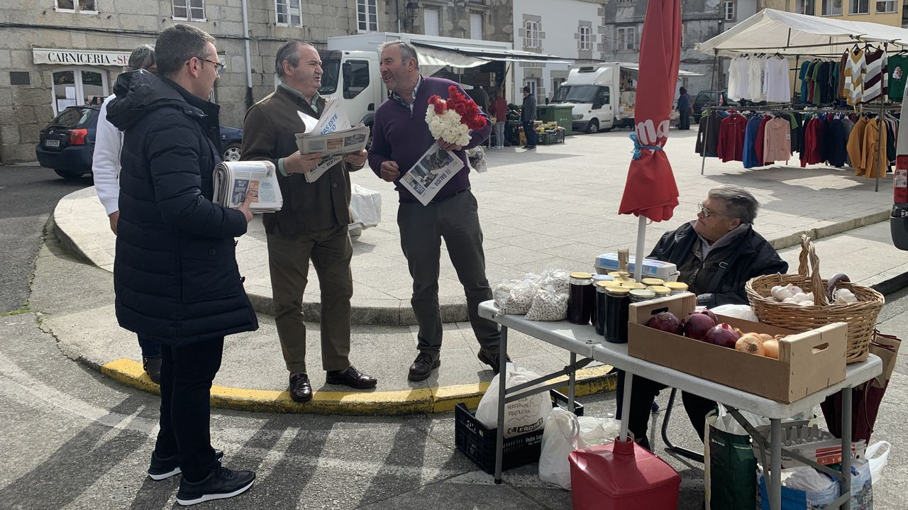 Vega y Balseiro, a la izquierda de la imagen, repartieron este sábado en el mercado de O Valadouro la publicación del PPdeG sobre Alberto Núñez Feijoo