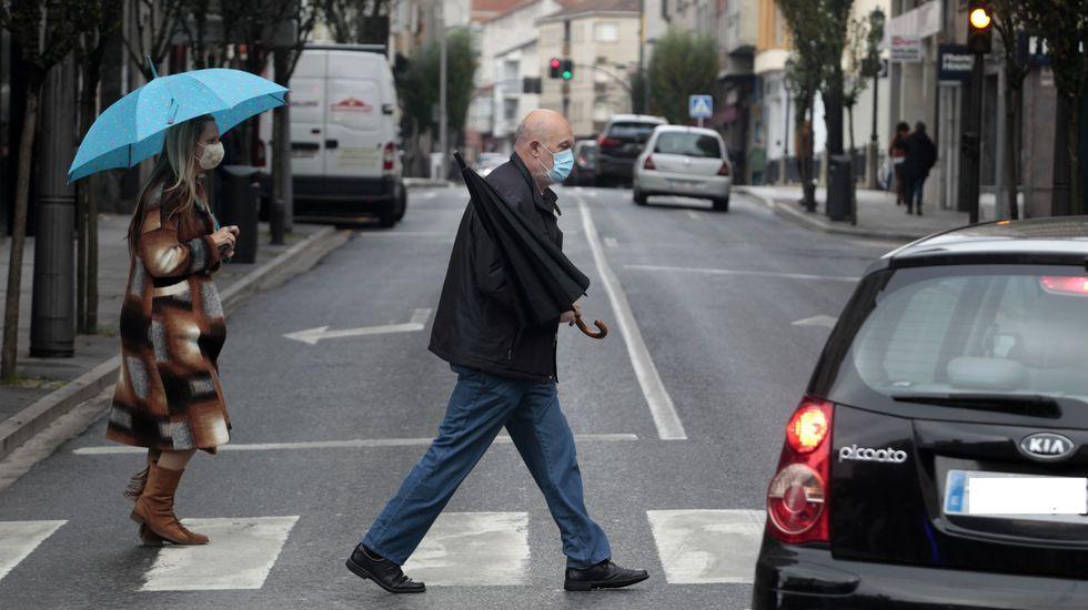 Transeúntes con mascarilla, este jueves en un paso de peatones de la avenida de Galicia