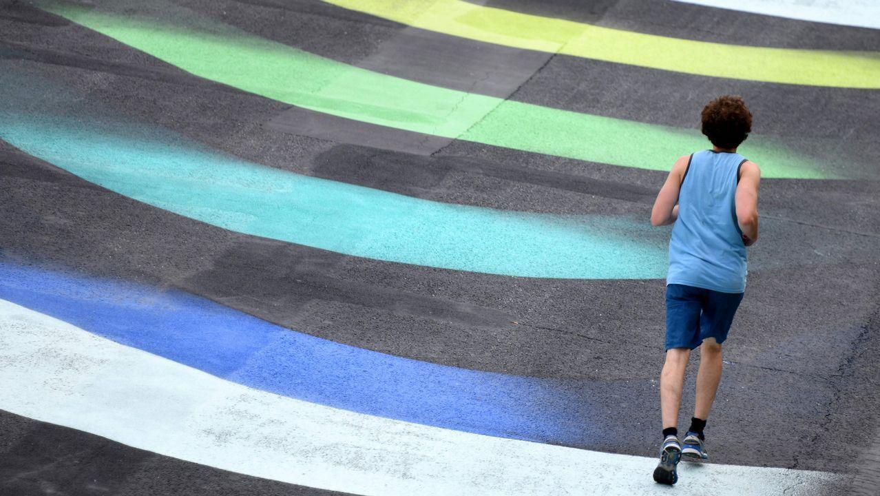Un corredor pasa sobre la obra del artista aleman 1010 titulada «Stream», en la orilla del río Sena, en París