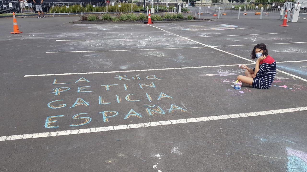 Allegra, de 12 años, recuerda sus orígenes gallegos con una pintada con tiza en el parking del hotel