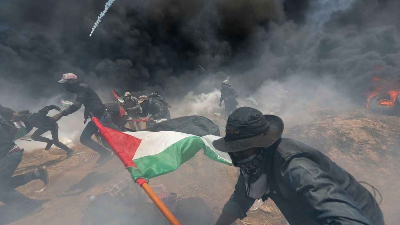 Un grupo de manifestantes palestinos corren para protegerse del fuego israelí en Gaza