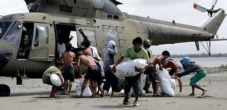Tercer aniversario del devastador tsunami de Japón.Supervivientes del tifón «Haiyan» descargan sacos con arroz de un helicóptero de las Fuerza Aérea filipina para repartir entre la población de la isla de Capiz.