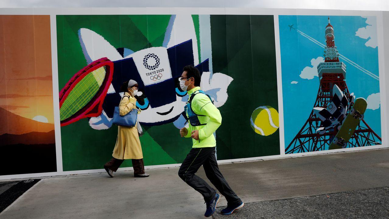 Un hombre con una máscara facial trota frente a una pared donde se representa a la mascota de los Juegos Olímpicos