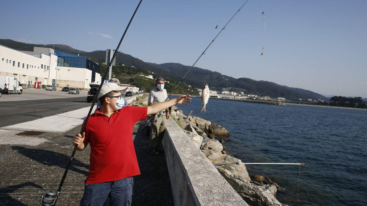 Un chaval izando un pez que capturó en Celeiro, en una imagen del pasado verano