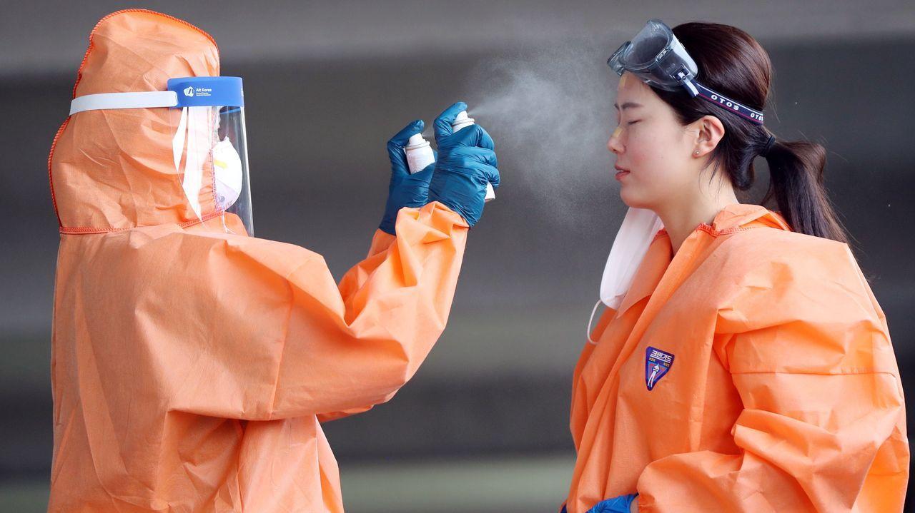 En Corea del Sur, un trabajador sanitario rocía con un esprai a una compañera durante un descanso