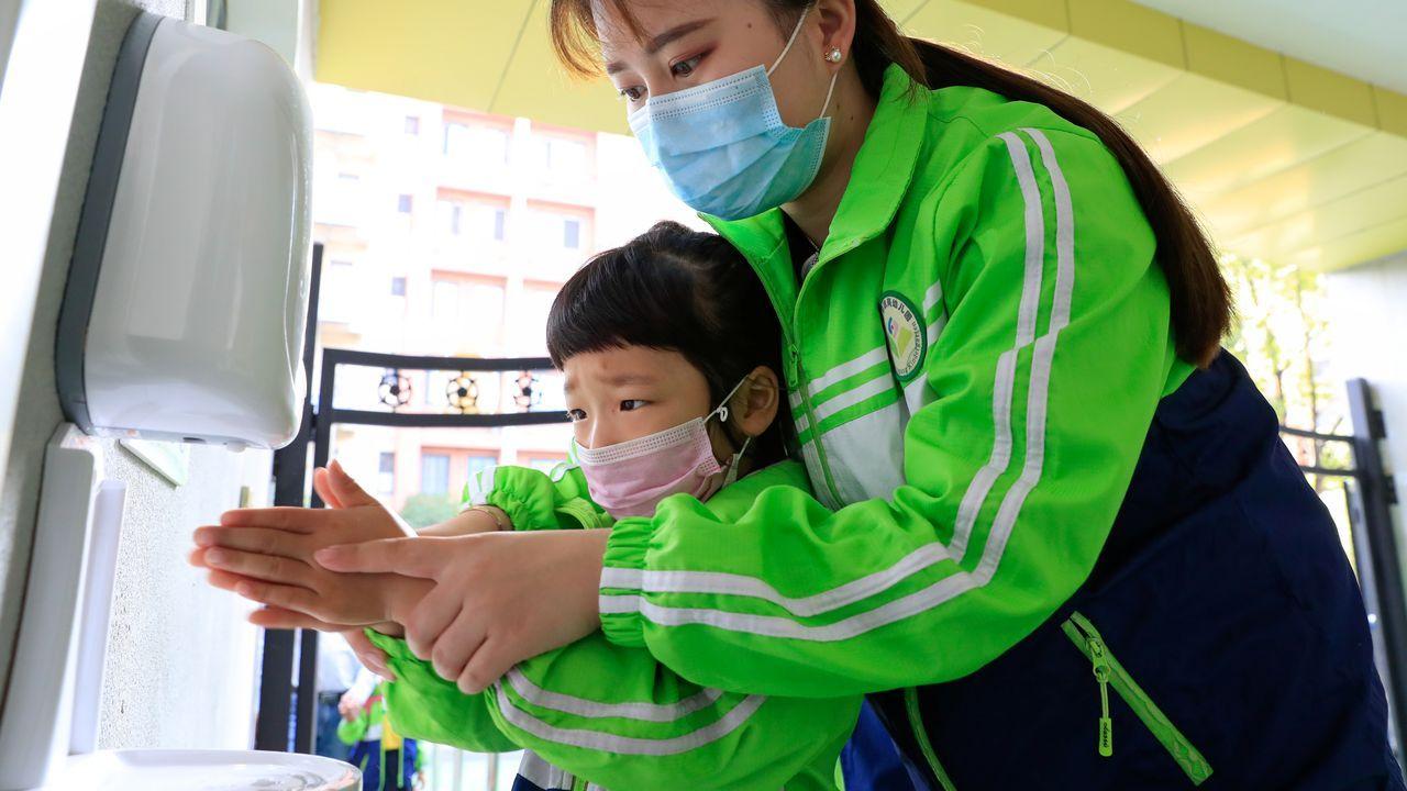 Un niño con mascarilla protectora se lava las manos en un colegio de China