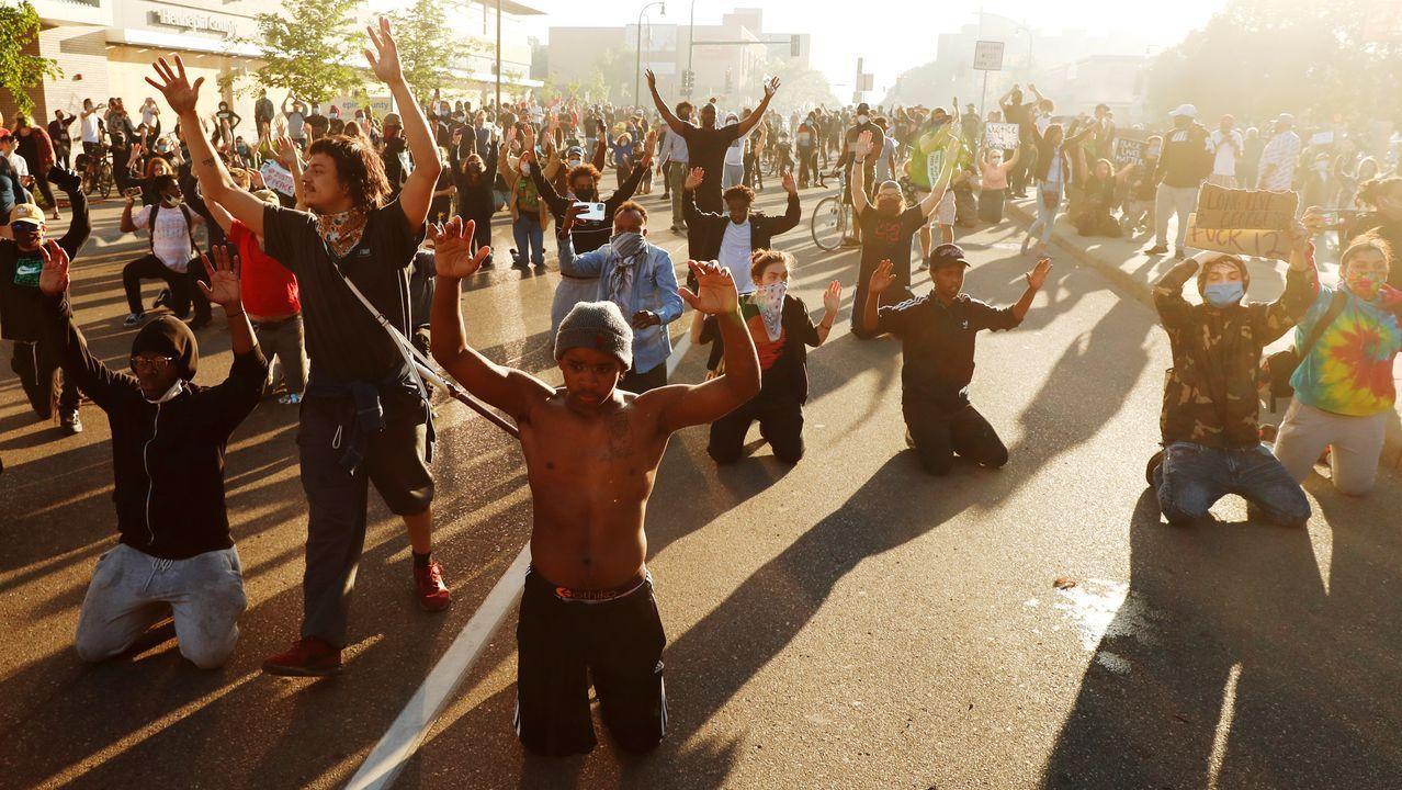 Un hombre arrodillado alza los brazos ante la llegada de agentes de la Guardia Nacional en Mineápolis