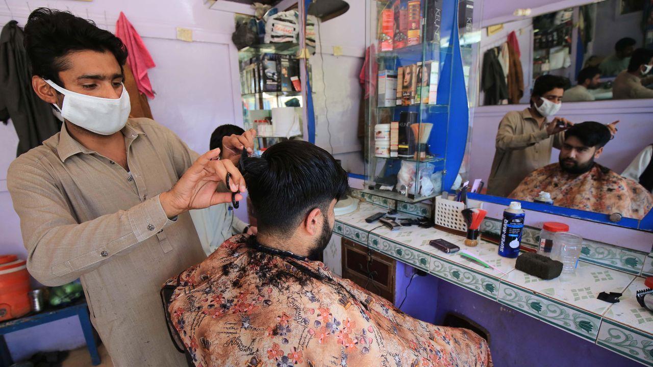 Un peluquero con mascarilla afeita a su cliente después de que algunas empresas pudieran operar, en Peshawar, Pakistán