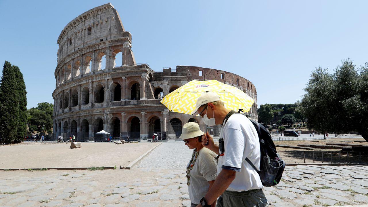 La gente pasa junto al Coliseo, en medio del brote de la enfermedad por coronavirus, en Roma, Italia