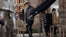 un camarero retira mesas de una terraza de Oviedo