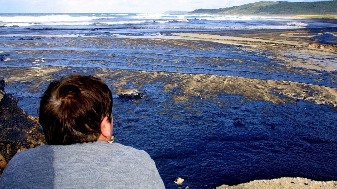 Un vecino observa el desastre ecológico que deja la marea negra en Laxe