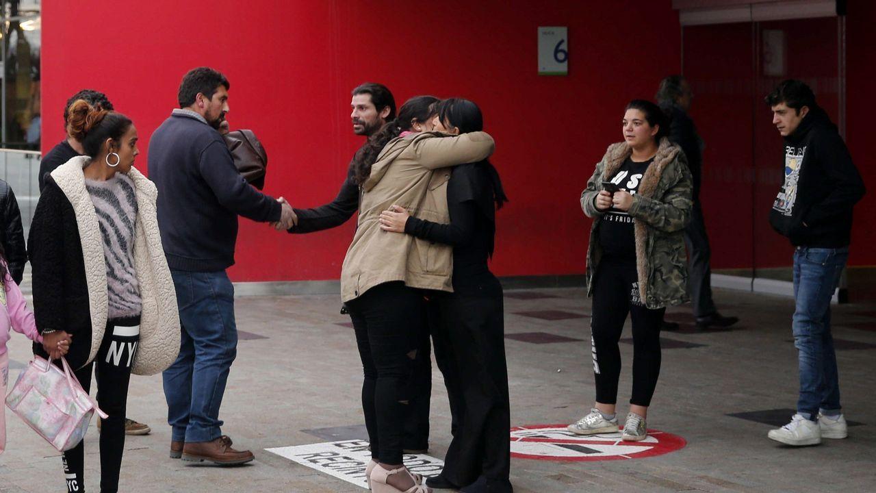 Familiares y amigos del interno de la prisión de Asturias al que los médicos dieron por muerto y que recobró ayer el conocimiento después de trasladarle al Instituto Anatómico Forense para practicarle la autopsia, conversan esta tarde en la entrada del Hospital Universitario Central de Asturias (HUCA).