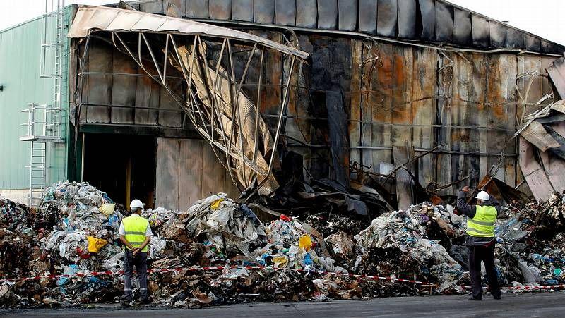 Una excavadora lucha contra las llamas en el incendio que sufrió la planta de Nostián.